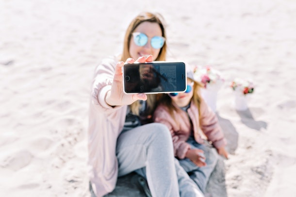 A woman and her niece sit on the beach, smile, and pose for a selfie.