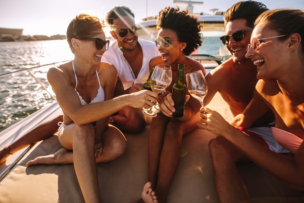 A group of friends laugh and toast their wine glasses on a boat at sunset.
