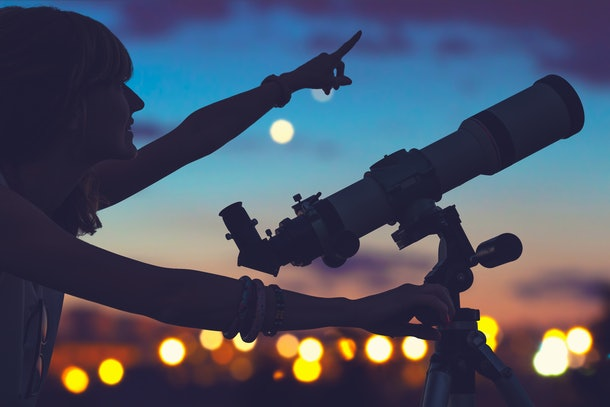 Girl looking at the stars with telescope beside her and de-focused city lights.