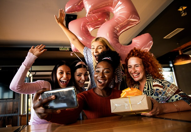 A group of friends all smile for a birthday selfie with a balloons and a present.