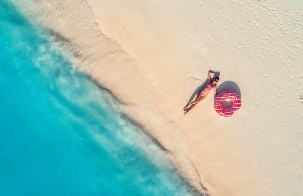 A woman lays on the sand next to a hot pink float and the blue ocean.