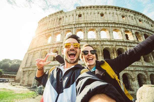 A happy couple snaps a selfie in front of the Colosseum in Rome.