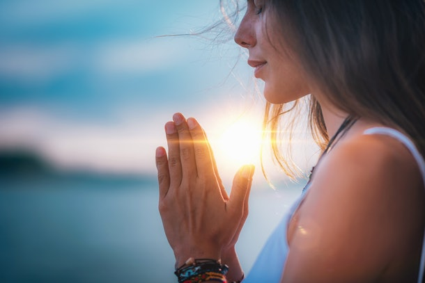 Young woman meditating with her eyes closed, practicing Yoga with hands in prayer position.
