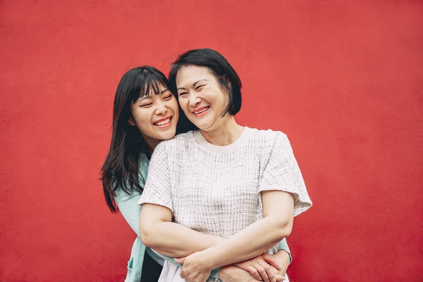 A happy asian mother and daughter hug in front of a red wall.