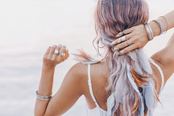 beautiful young boho woman close up with pink feathers and accessories at sunset