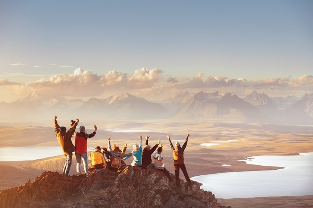 A big group of friends stand on top of a mountain peak overlooking a body of water at sunrise.