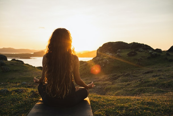 A woman meditates in a field during sunrise.