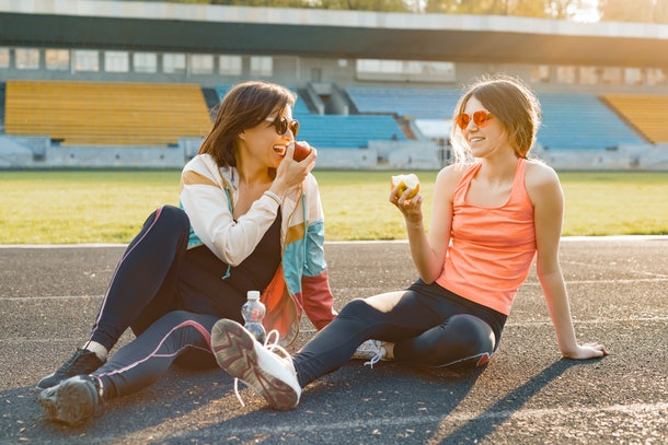 A mother and daughter wearing workout clothes sit on a track while eating apples on a sunny day.