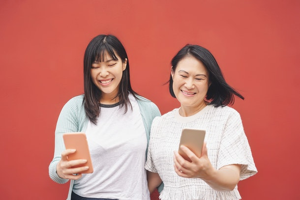 An Asian mother and daughter smile while looking at their cell phones and stand in front of a red wall.