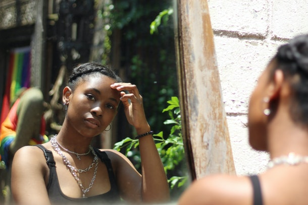 A beautiful African-American teenaged female model looking in a mirror outdoors