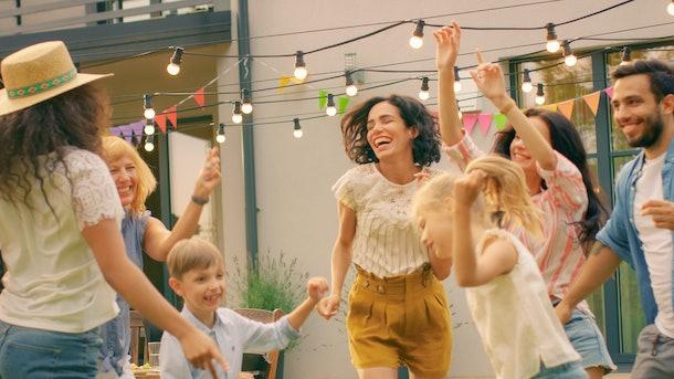 A big, happy family dances in the backyard.