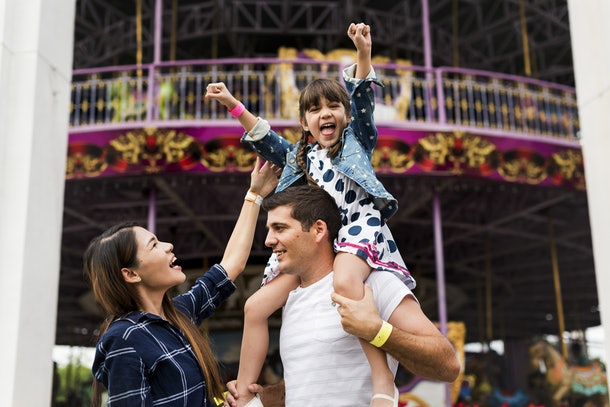 A happy little girl sits on her dad's shoulders at the carnival, while her mom smiles.