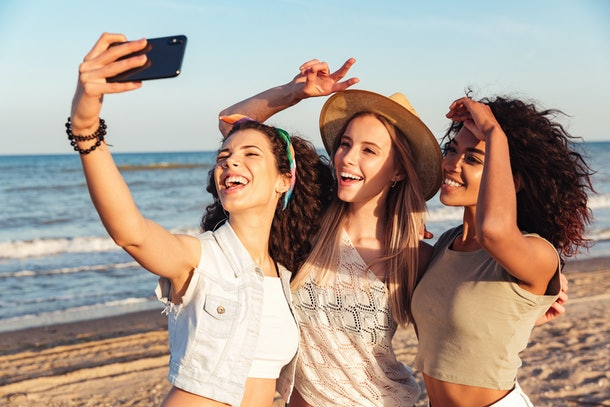Three happy girls friends in summer clothes taking a selfie at the beach