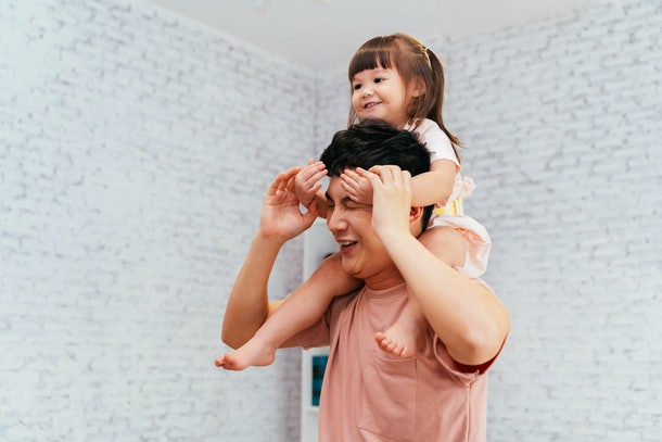 A dad gives carries his young daughter on his shoulders.