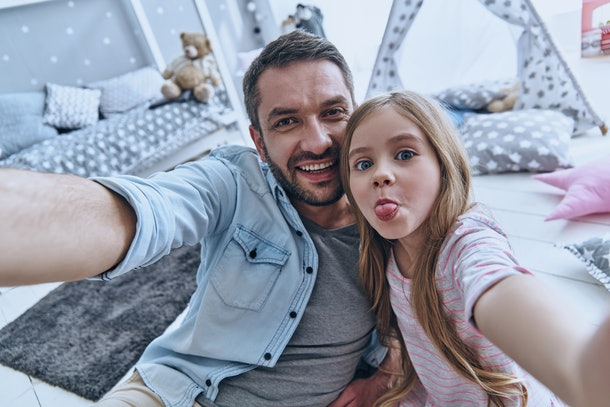 A father and young daughter make silly faces while taking a selfie at home.