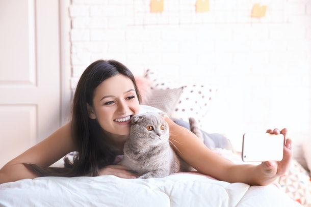 A happy woman takes a selfie with her cat.