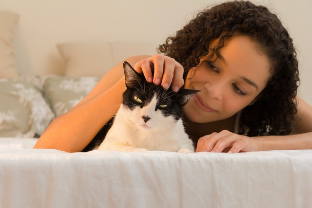 A woman laying in bed, pets her black and white cat on the head.
