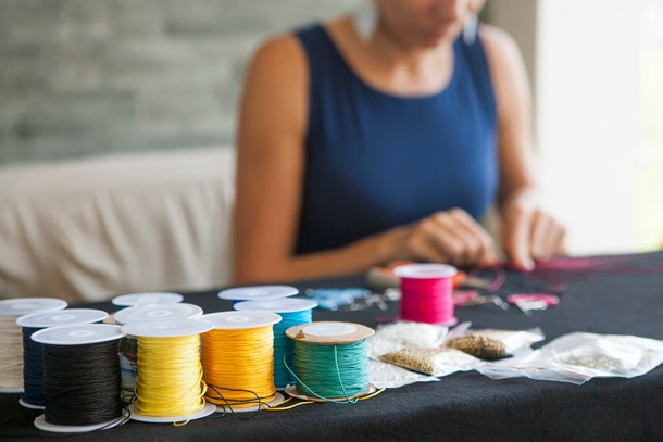 A woman makes some friendship bracelets with colorful string at home.