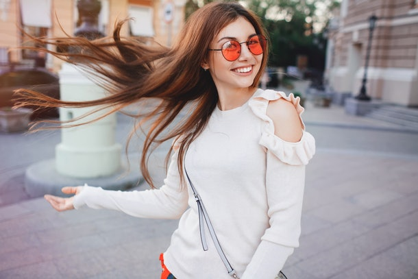 A happy brunette woman flips her hair, dressed in red sunglasses and a white sweater.