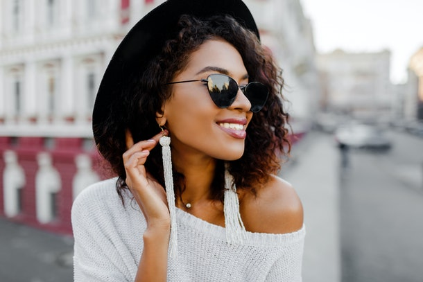 A fashionable woman wearing an off-the-shoulder white sweater, dangly white earrings, sunglasses, and a black felt hat smiles and looks off into the distance.