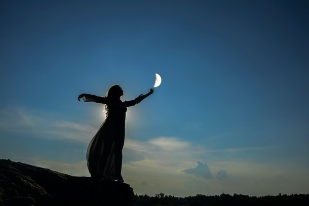 silhoutee of woman standing on top of mountain.  female hold in hand  growing moon above forest trees. backlight and moon light.