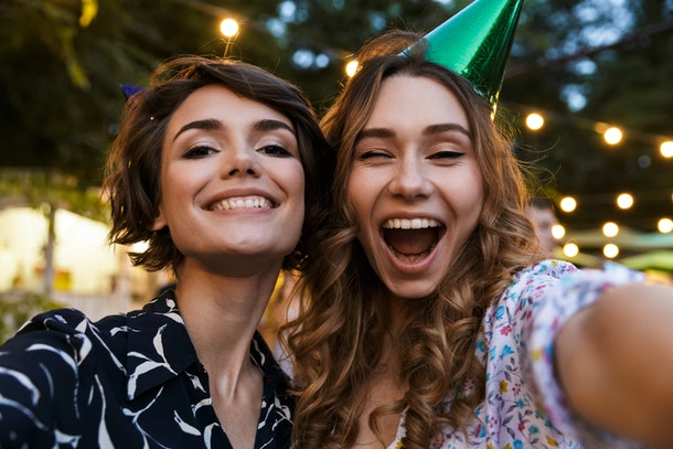 Two happy women pose for a birthday selfie outside.