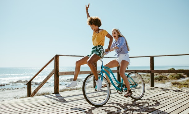 Two friends laugh while riding a bike on a boardwalk along the beach in the summer.