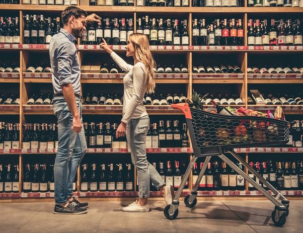 A trendy couple smiles while choosing wine in a liquor store.