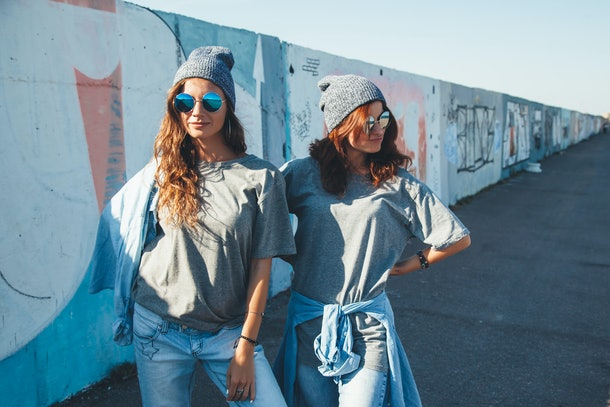 Two girls wearing gray T-shirts, gray beanies, and blue sunglasses stand in front of a wall outside.