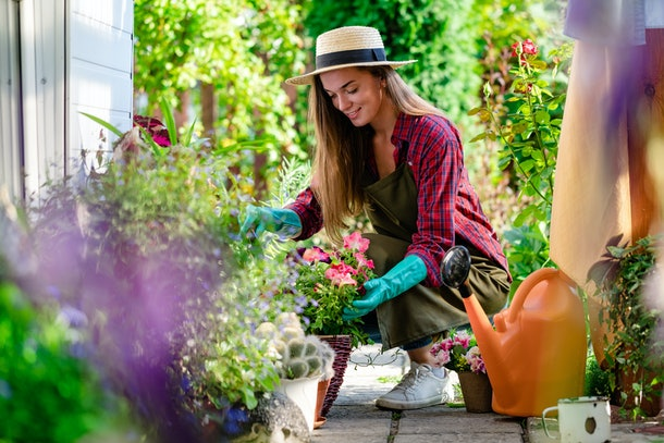 A woman, wearing a sunhat and teal gloves, tends to the plants in her home garden.