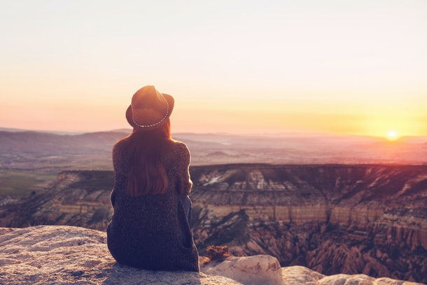 A view from the back of a girl in a hat sits on a mountain and admires the beautiful view and dawn or sunset in Cappadocia in Turkey.