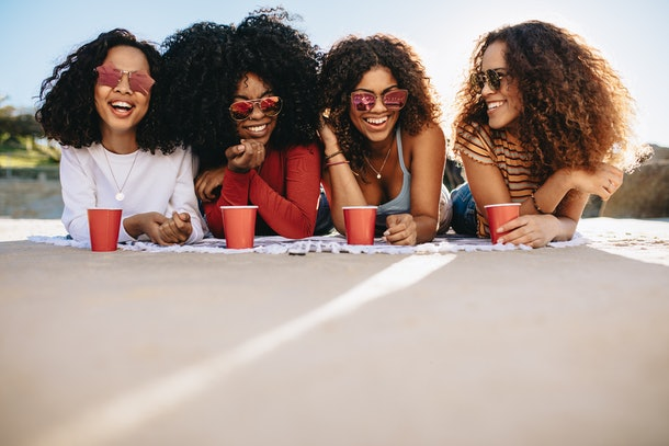 A group of friends wearing sunglasses and holding red cups lounge on the ground during a picnic in the backyard.
