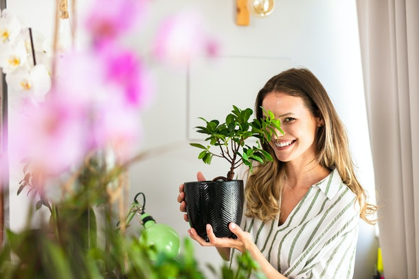 A happy woman holds up one of her potted plants at home.