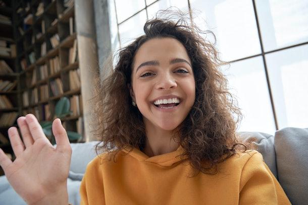 Happy hispanic latin gen z teen girl blogger smiling face waving hand talking to webcam recording vlog, social media influencer streaming, making video call at home. Headshot portrait. Webcamera view