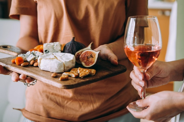A woman holds a cheese board, filled with snacks, while another set of hands hold a glass of wine.