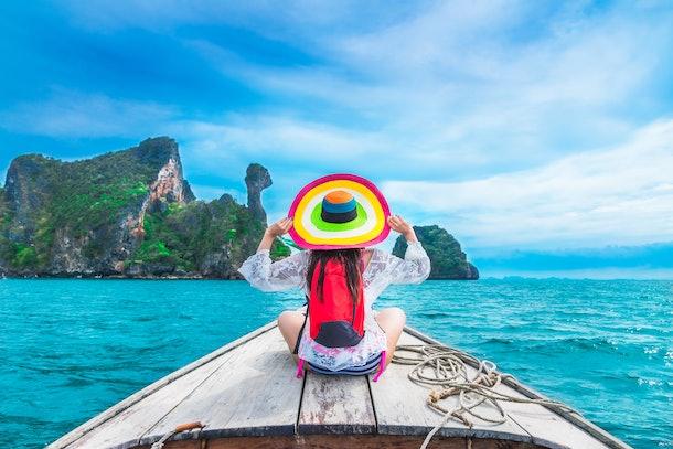 Summer lifestyle traveler woman in bikini and big hat joy relaxing on boat, Kai island, Andaman sea, Krabi, Travel Thailand, Beautiful destination landscape Asia, Summer holiday outdoor vacation trip