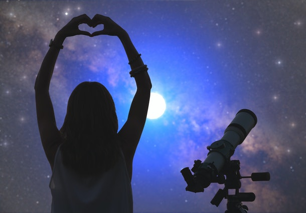 A woman makes a heart with her hands while stargazing at night.
