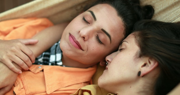 Beautiful diverse lesbian LGBT couple dating and cuddling together lying down in romance