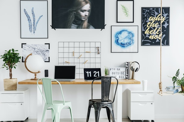 A decorated work from home desk has cute art on the wall.
