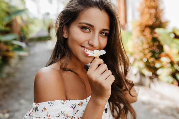 Woman enjoys scent of small white flower. Portrait of brunette with green eyes staring at camera on street