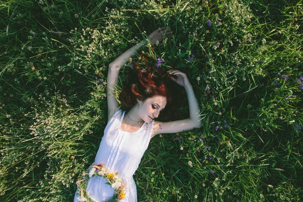 In spring, a young red-haired woman with a floral wreath  and in a white dress laying on a field on the grass and rests