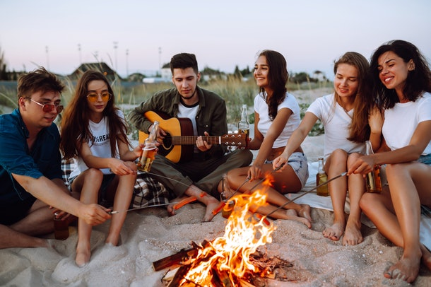 A group of friends hang out at the beach by a bonfire while roasting hot dogs and one plays the guitar.