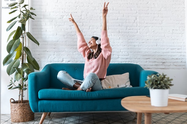 A happy woman in a pink sweater and jeans sits on a blue sofa while throwing up two peace signs with her hands.