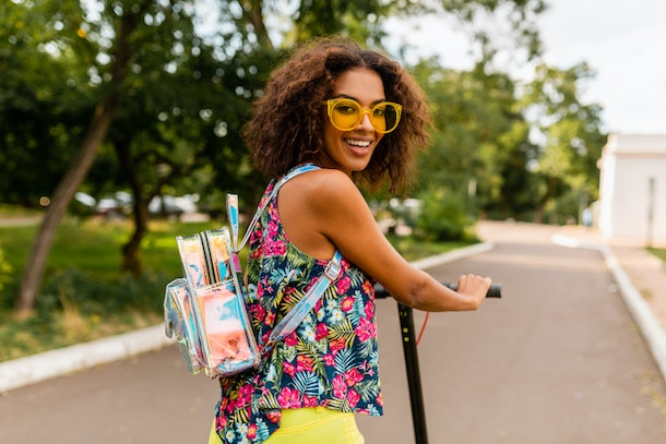 A stylish woman dressed in yellow sunglasses, a floral top, and yellow pants smiles while riding an electric scooter.