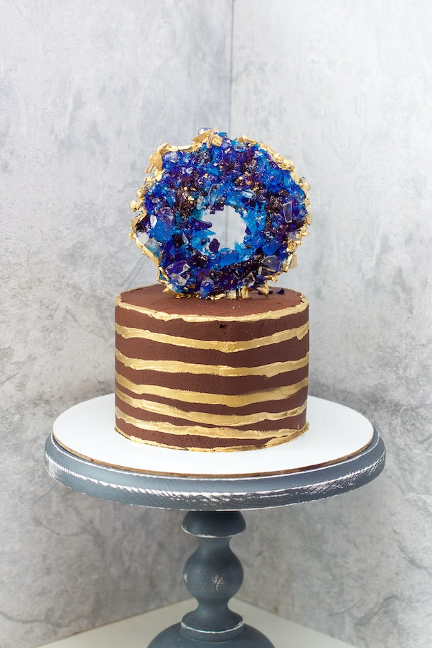 Chocolate modern cake with golden stripes and blue isomalt geode. Grey background.