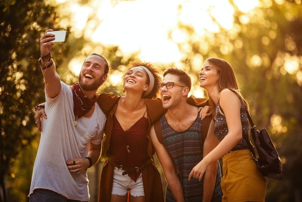 Group of friends taking selfie on their way to festival
