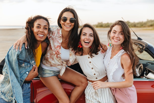 Picture of amazing young happy smiling cheery women friends posing near car outdoors at the beach.