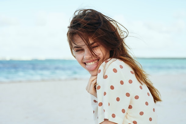 A happy woman wearing a white and brown polka dot shirt smiles while at the beach.