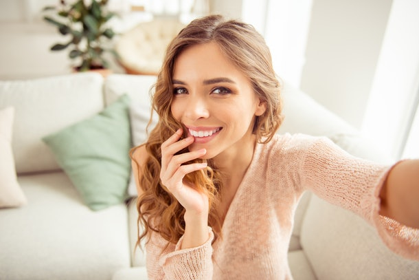 A woman in a pink sweater smiles and snaps a selfie.