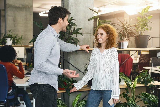 Young man and woman colleagues talking during working time in coworking space
